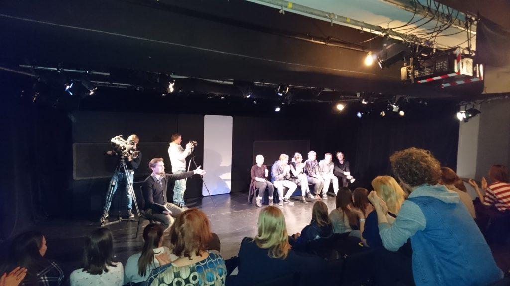 Ungdomar i publiken samtalar med skådespelare och regissör som sitter på en teaterscen, samtalet filmas.